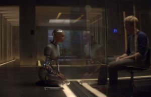 Caleb becomes Ava's inquisitor through plexiglas